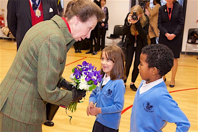 HRH is presented with a posy by two pupils of The Dolphin School.